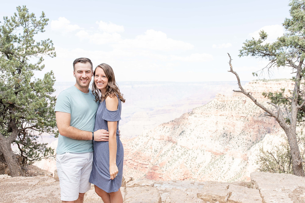 man and woman standing next to the Grand Canyon