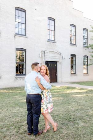 engagement photos couple hugging laughing journeyman distillery weddings three oaks michigan