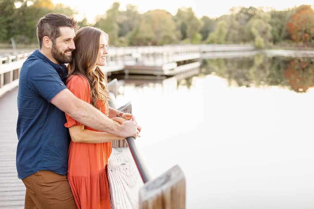 Cute couple standing smiling on bridge Pickerel Lake Park Grand Rapids engagement session