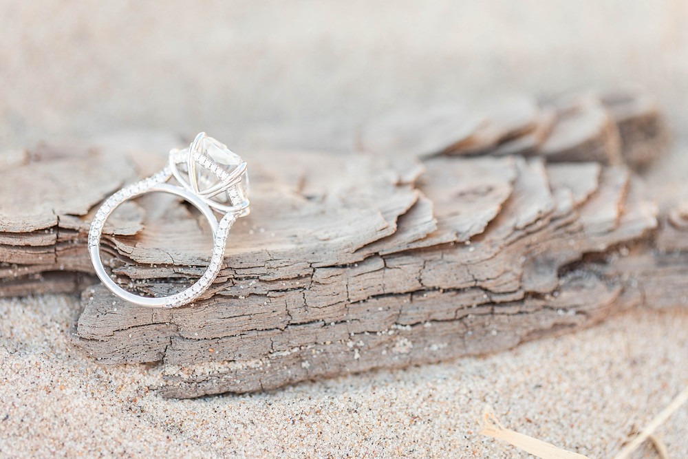 Engagement ring detail of side of ring on driftwood in sand South Haven Beach Michigan