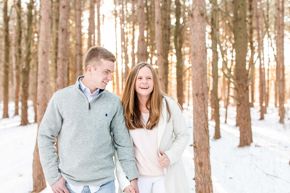 Josh and Andrea wedding photography husband and wife team michigan engagement session Al sabo land preserve couple smiling walking in snowy woods