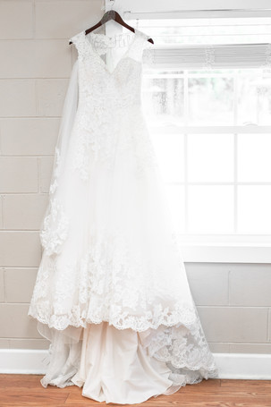 brides lace wedding dress hanging by window Milledgeville Georgia