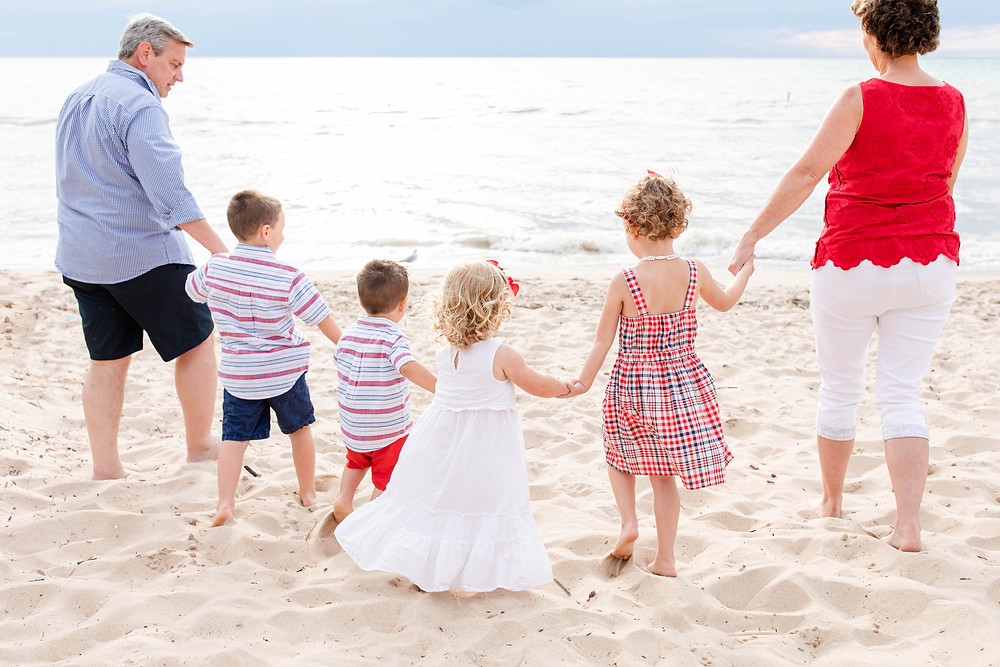 South Haven Family Shoot grandparents holding grandkids hands and walking on the beach Lake Michigan Red White and Blue Outfits