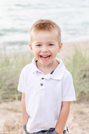 little boy laughing smiling on beach Lake Michigan South Haven Michigan