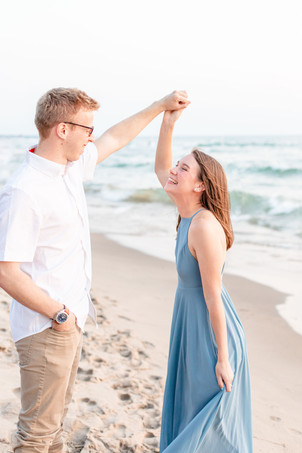 Engagement Photos Tunnel Park Beach Holland Michigan Engaged Couple twirling in long dress and laughing