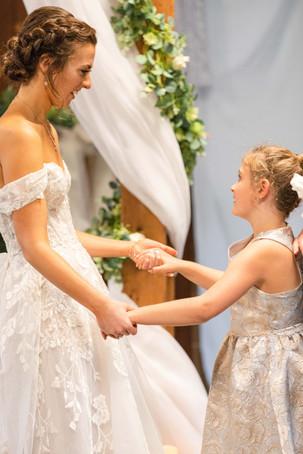 Bride and flowergirl smiling dancing Saint Patricks Park South Bend Indiana