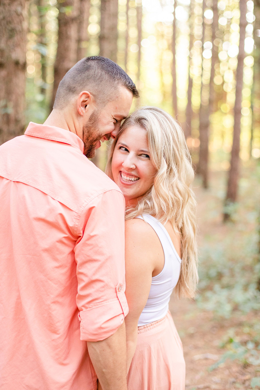 Engagement Photos Al Sabo Land Preserve Kalamazoo Michigan cute couple snuggling smiling in Tall row of Pines