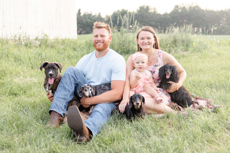 cute family photo shoot daughter smiling sitting grass spring dogs