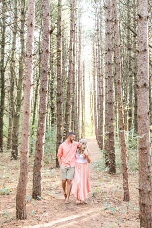 Engagement Photos Al Sabo Land Preserve Kalamazoo Michigan cute couple walking and laughing in Tall row of Pines