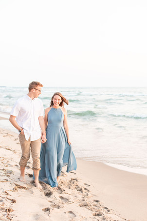 Engagement Photos Tunnel Park Beach Holland Michigan Engaged Couple holding hands walking on beach