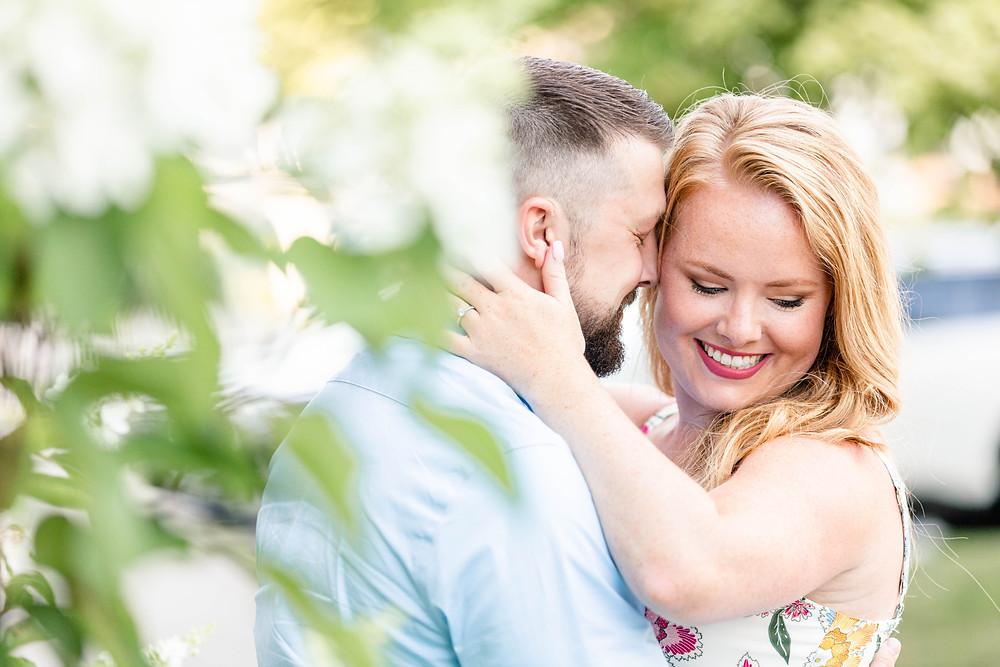 engagement photos couple snuggling flower bush journeyman distillery weddings three oaks michigan