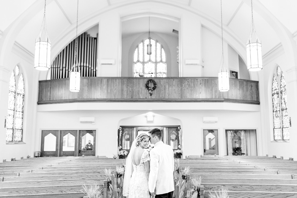 josh and Andrea photography husband and wife team michigan winter wedding south haven st basils bride and groom standing in sanctuary