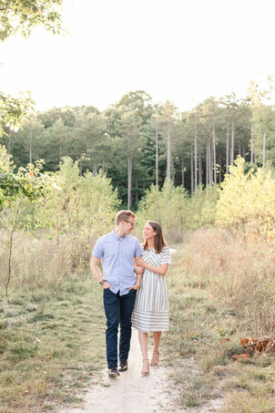 Engagement Photos Riley Trails Holland Michigan Engaged Couple walking down path tall pine trees