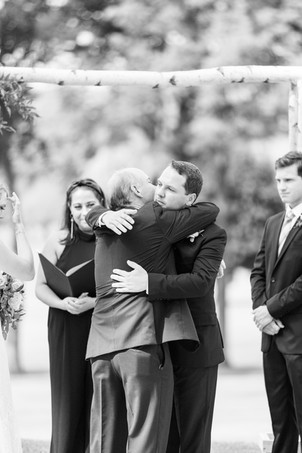 groom and brides dad hugging ceremony Kent Country Club Wedding Grand Rapids