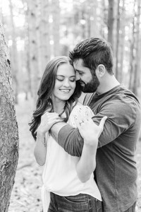 Cute couple in woods smiling provin trails Grand Rapids engagement session