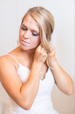 bride putting on earrings Kent Country Club Wedding Grand Rapids