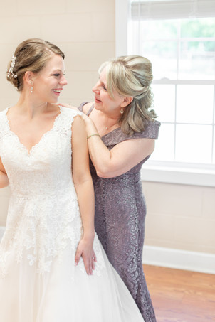 mom mother buttoning back of brides smiling at daughter wedding dress Milledgeville Georgia