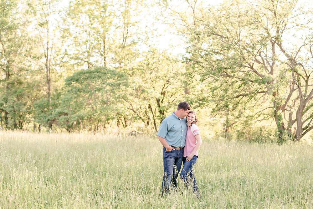 cute couple open field grass snuggle standing Something Blue Berry Farm Wedding Venue