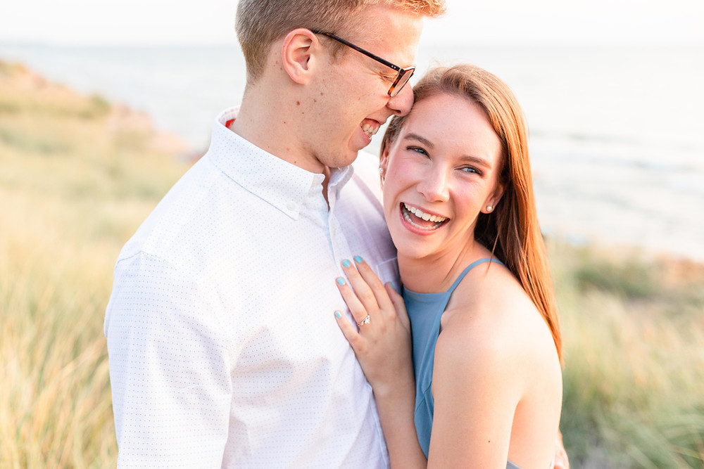 Engagement Photos Tunnel Park Beach Holland Michigan Engaged Couple laughing standing in dune grass