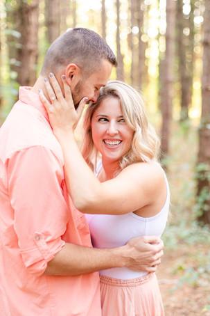 Engagement Photos Al Sabo Land Preserve Kalamazoo Michigan couple hugging and smiling in Tall row of Pines