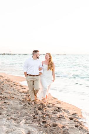 white dress engagement photos cute couple walking holding hands on city beach new buffalo michigan