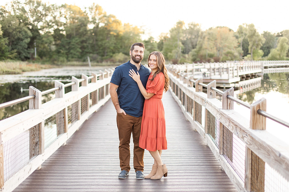 Cute couple smiling standing on bridge Pickerel Lake Park Grand Rapids engagement session