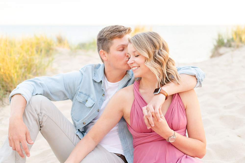 south haven man and women smiling sitting beach engagement photos