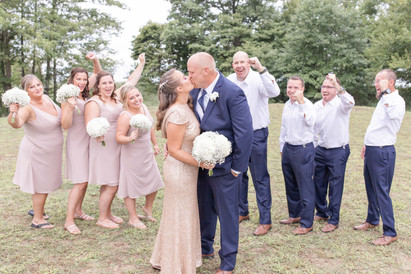bridal party celebrating bride and groom kissing south haven beach wedding