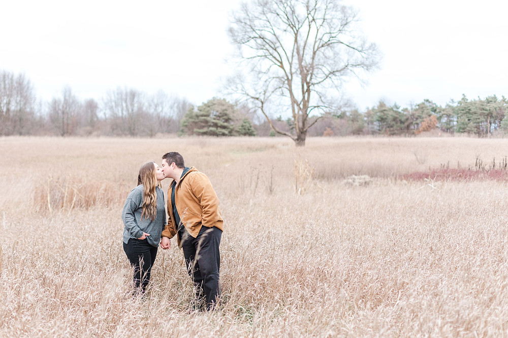 josh and Andrea photography husband and wife team michigan engagement photo shoot al sabo land preserve man and woman kissing standing in field