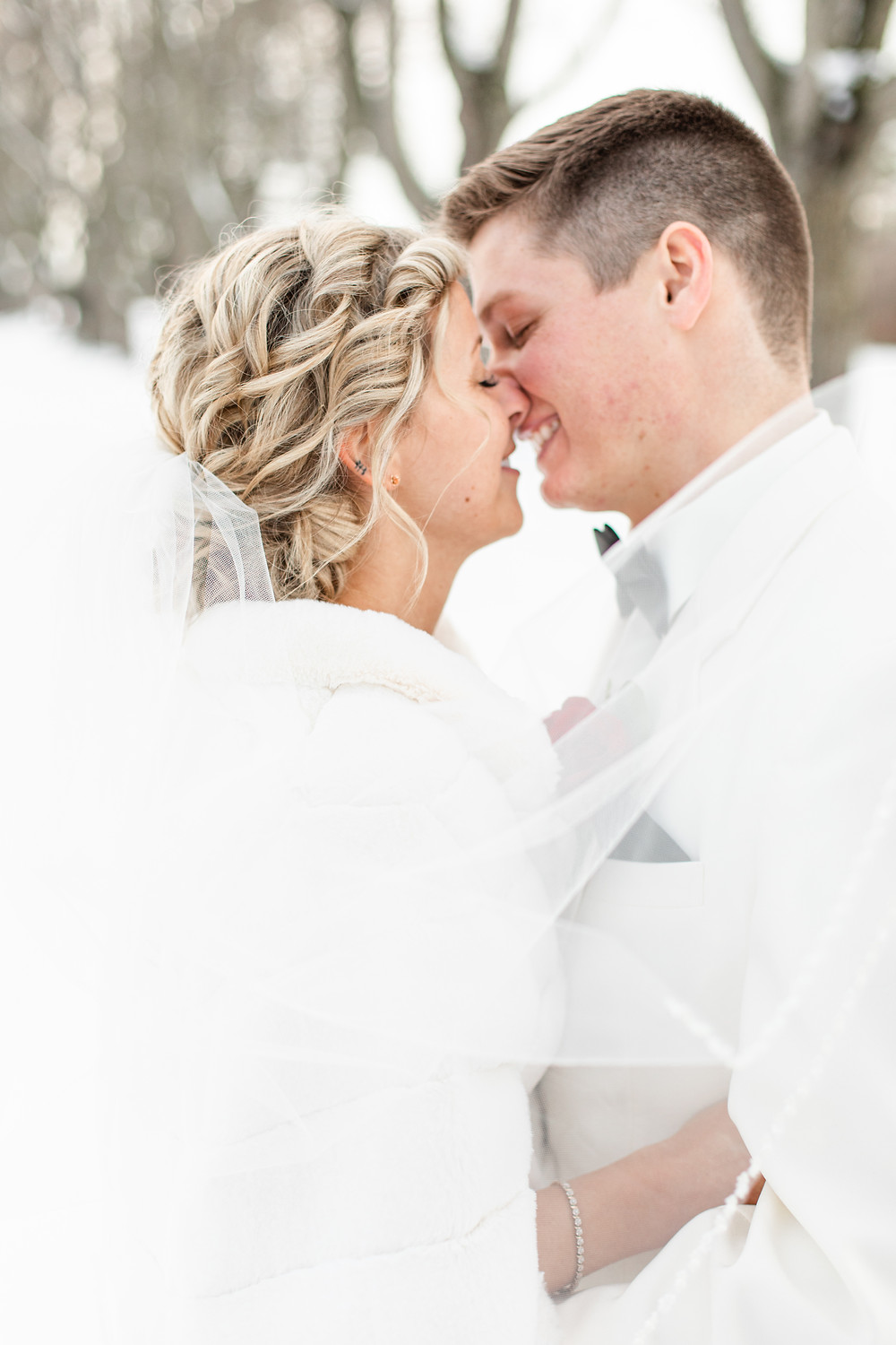 josh and Andrea photography husband and wife team michigan winter wedding south haven bride and groom kissing in snow forest