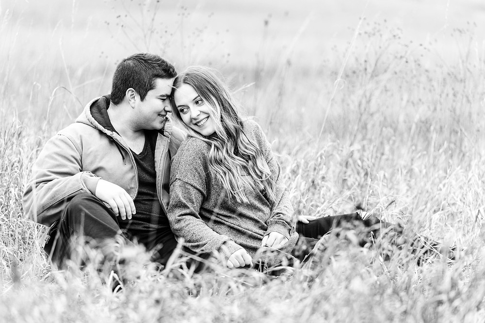 josh and Andrea photography husband and wife team michigan engagement photo shoot al sabo land preserve man and woman black and white sitting smiling in field