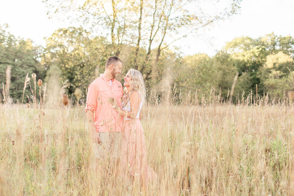 Engagement Photos Al Sabo Land Preserve Kalamazoo Michigan Open Field cute couple smiling looking at eachother