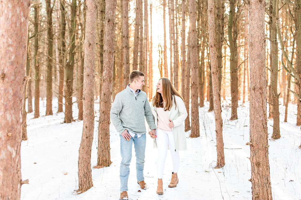 Josh and Andrea wedding photography husband and wife team michigan engagement session Al sabo fiance couple walking in woods smiling laughing