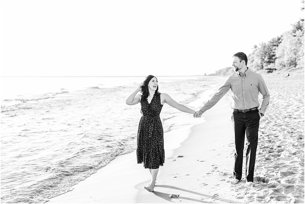 Josh and Andrea wedding photography husband and wife photographer team michigan pictures Lake Harbor Park engagement pictures session photo shoot fiance walking beach
