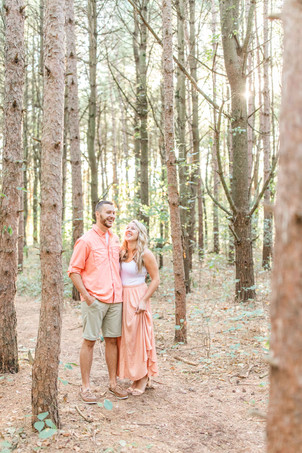 Engagement Photos Al Sabo Land Preserve Kalamazoo Michigan cute couple laughing together in Tall row of Pines