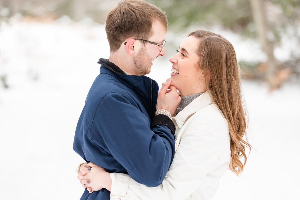 Josh and Andrea wedding photography husband and wife team michigan Grand Haven Rosy Mound engagement session fiance snowy forest woods kissing