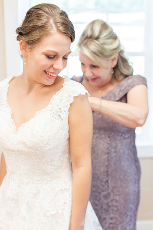 mom mother buttoning back of brides wedding dress Milledgeville Georgia