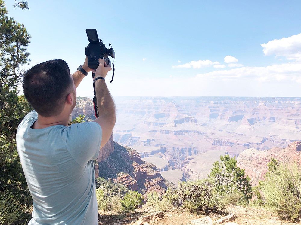 man holding camera taking picture of Grand Canyon