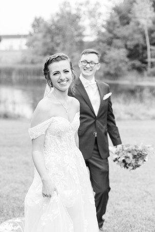 Bride and Groom smiling walking Bridal bouquet fall colors Saint Patricks Park South Bend Indiana
