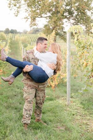 Engagement photos Round Barn Winery Baroda Michigan vineyard guy picking up girl