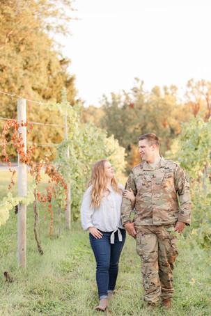 Engagement photos Round Barn Winery Baroda Michigan walking in vineyard cute couple