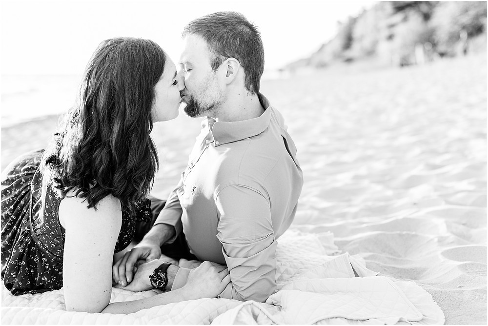 Josh and Andrea wedding photography husband and wife photographer team michigan pictures Lake Harbor Park engagement pictures session photo shoot fiance beach laying down