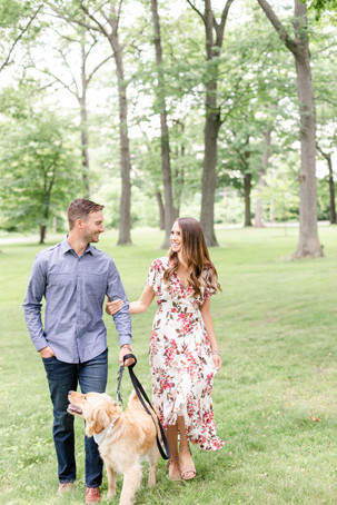 engaged cute couple walking with dog at the Rivere Park Midland Michigan