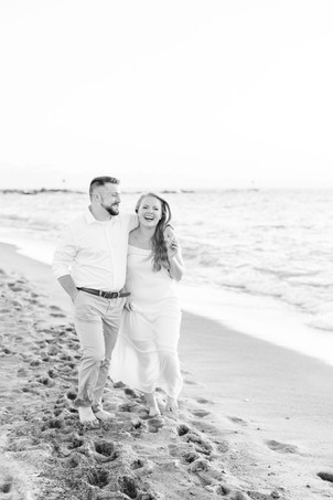 white dress engagement photos cute couple walking laughing arms around each other on city beach new buffalo michigan
