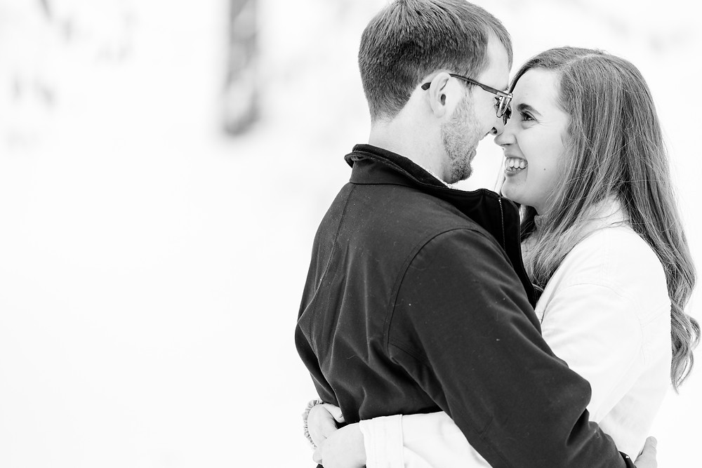 Josh and Andrea wedding photography husband and wife team michigan Grand Haven Rosy Mound engagement session fiance snowy forest woods standing smiling