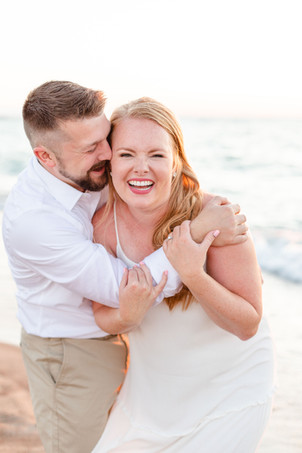 white dress engagement photos cute couple hugging laughing on city beach new buffalo michigan