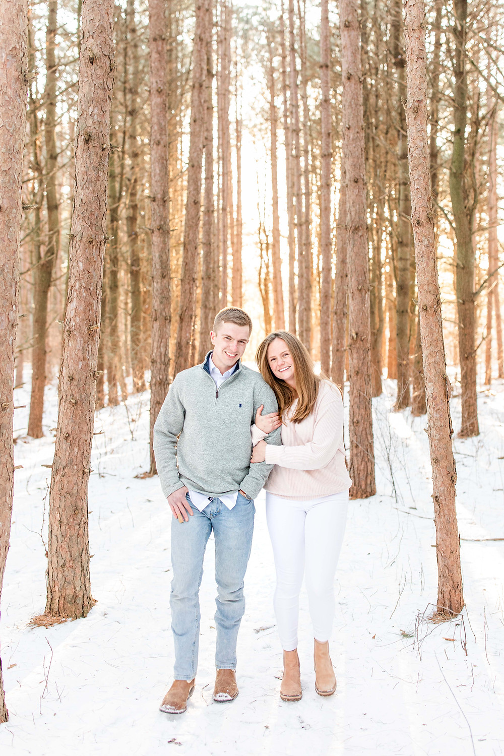 Josh and Andrea wedding photography husband and wife team michigan engagement session Al sabo land preserve couple standing smiling in snowy woods