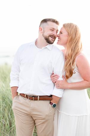 white dress engagement photos cute couple snuggling on city beach new buffalo michigan