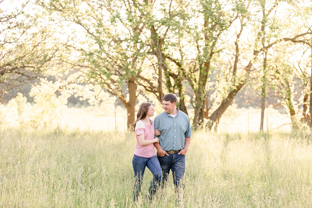 engaged couple walking open grassy field Something Blue Berry Farm Wedding Venue