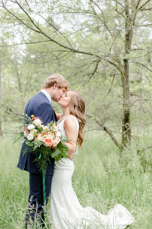 bride and groom standing in field kissing in the details byron center truer design